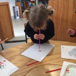 India-Rose uses a straw to blow the paint around the page.